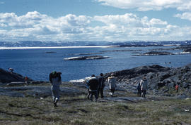 Photograph of a group of people walking towards the water in Frobisher Bay, Northwest Territories