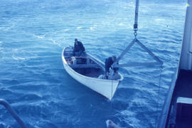 Photograph of two men and a small boat collecting mail in Emily Harbour, Newfoundland and Labrador