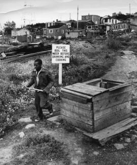 Photograph of a person walking by a well in Africville