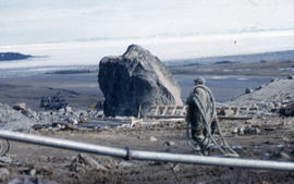 Photograph of an unidentified man and construction equipment in Frobisher Bay, Northwest Territories