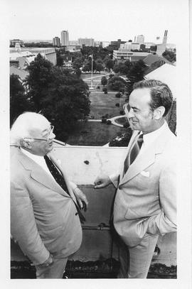 Photograph of Henry Hicks and an unidentified person standing on the roof of the Henry Hicks Acad...