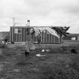 Photograph of a woman hanging laundry on a clothesline in Fort Chimo, Quebec