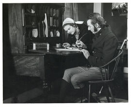 Photograph of a woman in contemporary dress conferring with actor David Murray, in period costume...