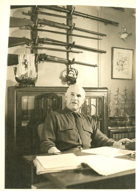 Photograph of Thomas Head Raddall captured mid-speech, sitting at his desk in his study