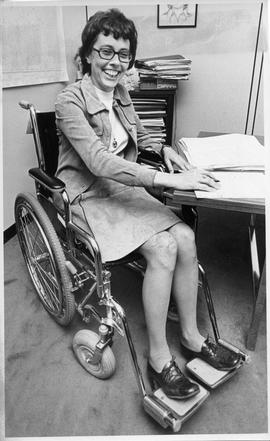 Photograph of Constance Glube sitting in a wheelchair at a desk