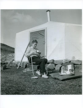 Photograph of Barbara Hinds sitting outside a tent and drinking tea