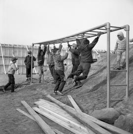 Photograph of children playing on monkey bars in Fort Chimo, Quebec