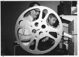 Photograph of Ted Coffin and Irving Kirk setting up a movie projector