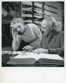Photograph of Edith and Thomas Head Raddall smoking and editing a typed manuscript together in Ra...