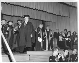 Photograph of a crowd of unidentified people in robes on stage