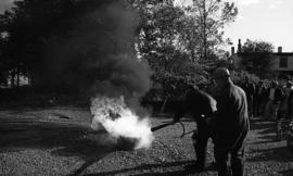 Photograph of an unidentified person putting out a fire with a fire extinguisher