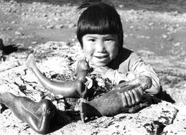 Photograph of a child with three carvings of a sea goddess