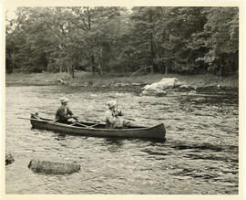 Photograph of two men reeling a fish and prepping a net from a canoe on Mersey River near Maitlan...