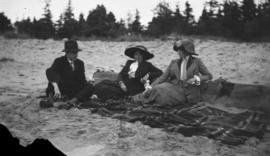Two women and a man sitting on a beach