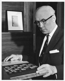 Photograph of Henry Hicks with a stamp collection