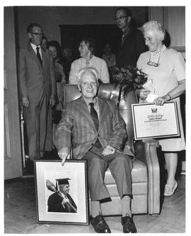 Photograph of James Stoker and Mrs. Stoker holding a framed photograph and certificate