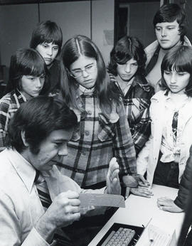 Photograph of a man showing a computer punch card to a group of children