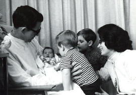 Photograph of introducing baby to two young children