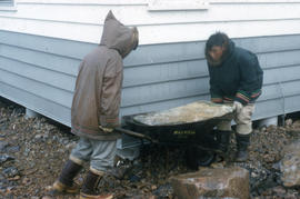 Photograph of two people moving a stone with a wheelbarrow