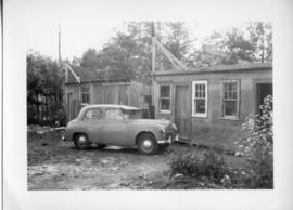 Photograph of a car and two sheds