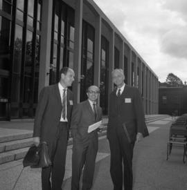 Photograph of three unidentified people standing in front of the Tupper Building