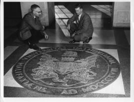 Photograph of two men with the bronze seal in the Arts & Administration Building
