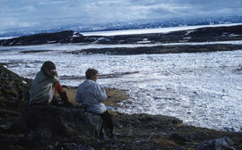 Photograph of Barbara Hinds and another woman sitting on a rock