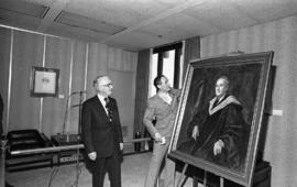 Photograph of Chester Stewart looking at a painting of himself