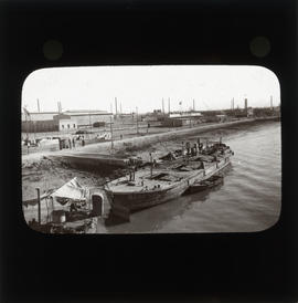 Photograph of a boat next to unidentified buildings