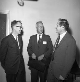 Photograph of three unidentified people at an event for the Dalhousie medical centennial