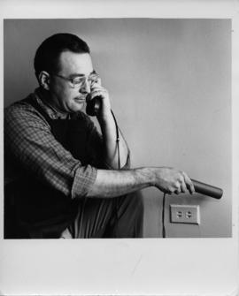 Photograph of R.K. Jones holding a phone to his ear