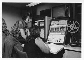 Photograph of two unidentified people operating television equipment