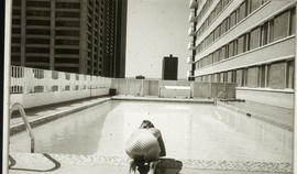 Photograph of a woman sitting next to a pool
