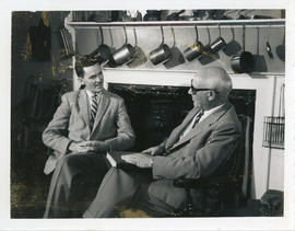 Photograph of Lloyd MacInnis interviewing Thomas Head Raddall, who is holding a book and wearing ...