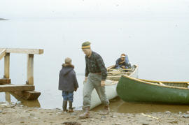 Photograph of Bob Green and two other people with canoes in Frobisher Bay, Northwest Territories