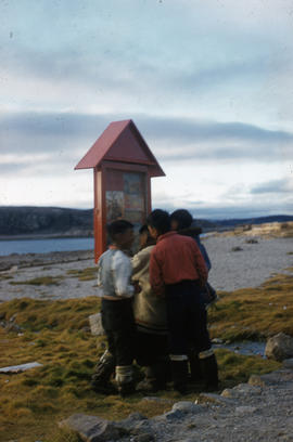 Photograph of children looking at a sign in Cape Dorset, Northwest Territories