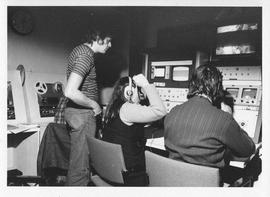 Photograph of three unidentified people at a switchboard