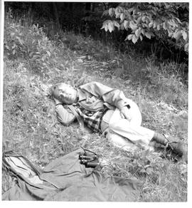 Photograph of an unidentified man resting on the ground