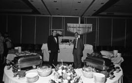Photograph of two unidentified people with a buffet