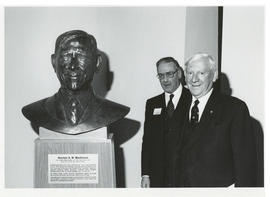 Photograph of Norman A. M. MacKenzie with a bust of himself