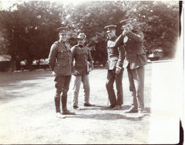Photograph of four officers in uniform standing on a lawn at Hythe, England