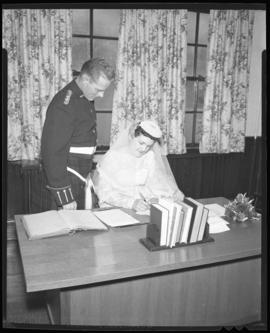 Photograph of Mr. & Mrs. Leil signing wedding documents
