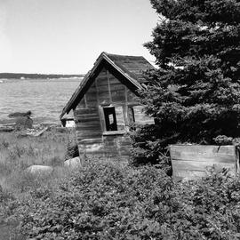 Photograph of an old shed on a shore