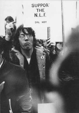 "Photograph of Will Offley pointing to his ""Support the N.L.F."" (National Liberation Front) sign d..."