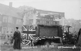 Postcard replica of photograph of a parade float bearing a model of the original Dalhousie Colleg...