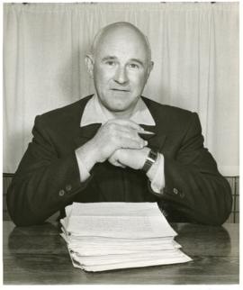 Portrait of Thomas Head Raddall in his study, marking a stack of papers