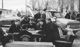 Photograph of students playing cards outside the Student Union Building, blocking a tow truck dri...