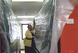 Photograph of Betty Sutherland holding tarps after the Kellogg Library flood 2004