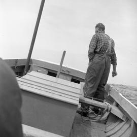 Photograph of an unidentified man standing on a boat