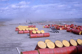 Photograph of several red barrels in a dust storm